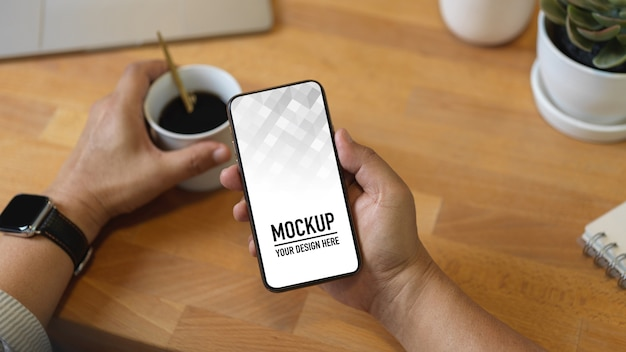 Close up view of male hand holding smartphone mockup and coffee cup on wooden table