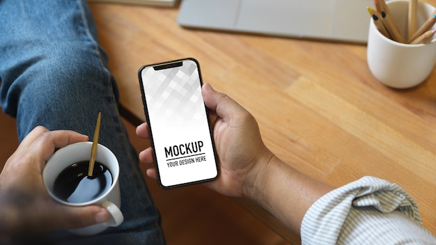 Close up view of male hand holding smartphone mockup and coffee cup