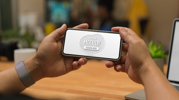 Close up view of male hands holding mock up horizontal smartphone screen in workplace