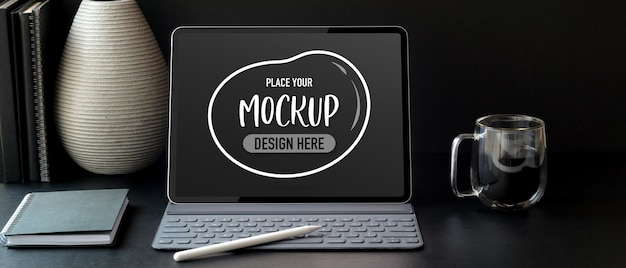 Close up view of mock up digital tablet on black table with coffee cup and office supplies Premium Psd