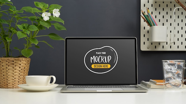 Close-up view of mock up laptop on working table with coffee cup and decorations in workspace