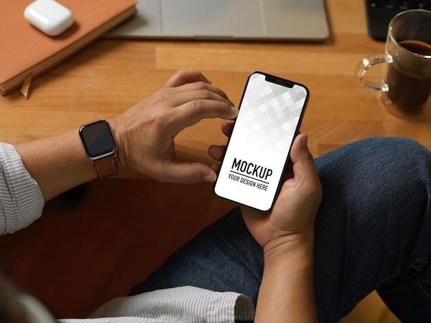 Крупным планом вид руки бизнесмена, использующей макет смартфона, сидя на рабочем месте