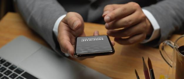 Крупным планом вид рук бизнесмена, использующего макет смартфона