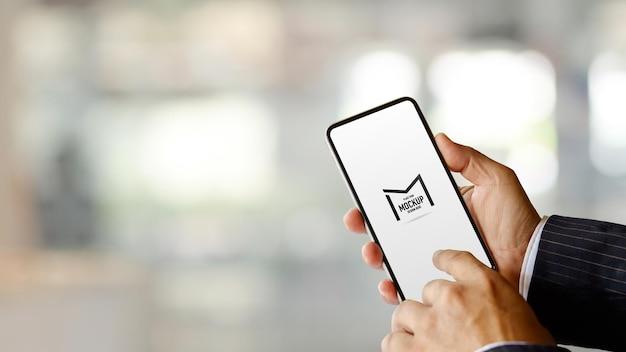 スマートフォンのモックアップを使用してビジネスマンの手のビューをクローズアップ
