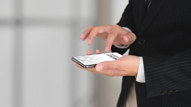 스마트 폰 모형을 사용하여 검은 정장 손에 사업가의보기를 닫습니다