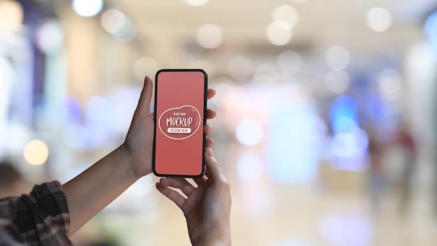 スマートフォンのモックアップを持っている女性の手のクローズアップ表示