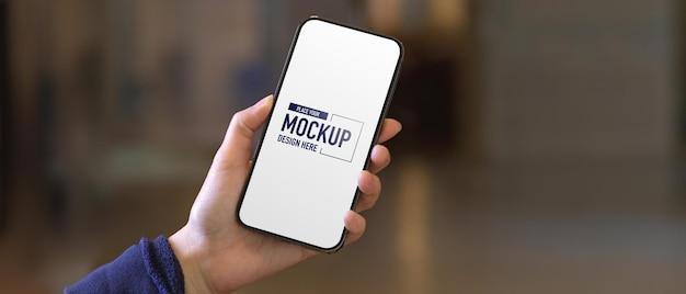 モックアップ画面でスマートフォンを持っている女性の手のクローズアップビュー