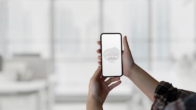 Крупным планом вид женских рук, держащих макет смартфона на размытом фоне
