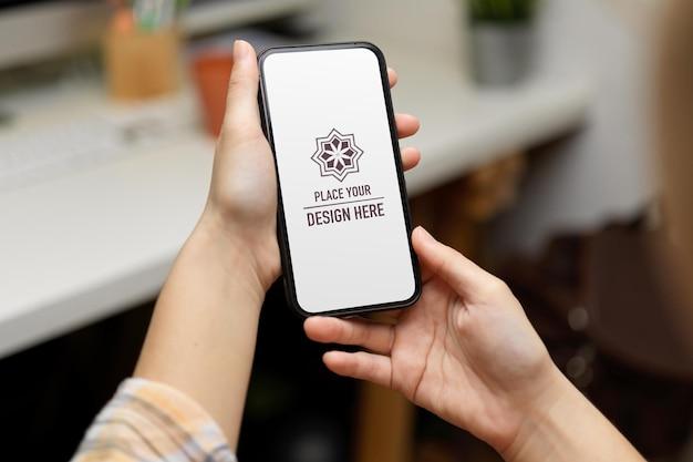スマートフォンのモックアップを保持している女性の手のクローズアップ