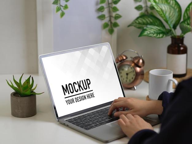 ノートパソコンのモックアップで入力する女性の手のビューを閉じる