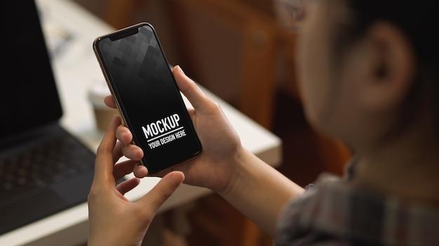 オフィスルームで作業中にスマートフォンのモックアップを使用して女性のクローズアップビュー