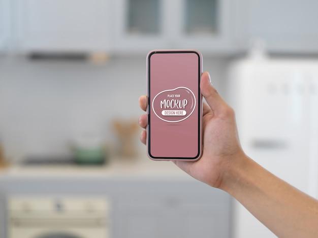 Крупным планом вид руки, держащей макет смартфона