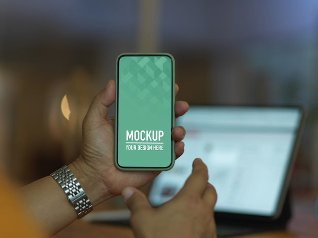 Крупным планом вид мужской руки, держащей макет смартфона