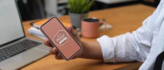 作業台に座りながらスマートフォンを模擬的に表示するために保持している男性の手のクローズアップ表示