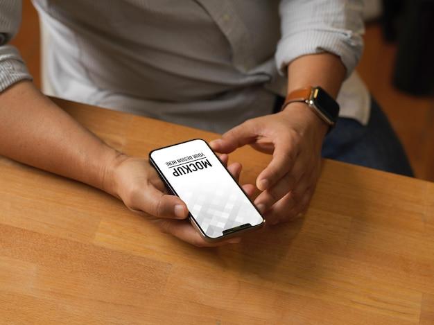 Крупным планом вид мужских рук, использующих макет смартфона