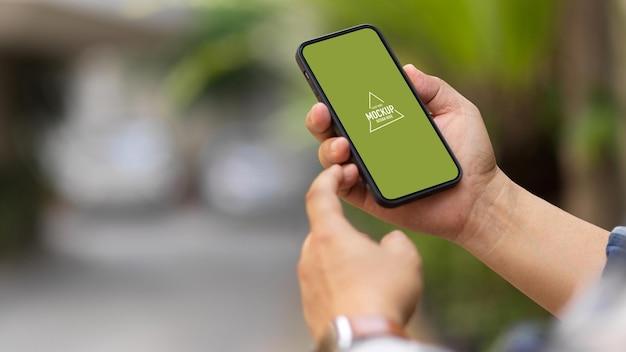 スマートフォンのモックアップを使用して男性の手のクローズアップ