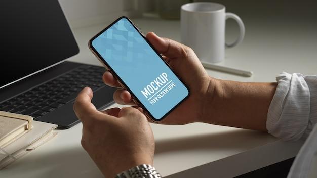 Крупным планом вид мужчины, держащего макет смартфона