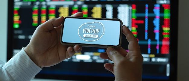 作業机で水平型スマートフォンをモックアップを保持している男性会社員のクローズアップ表示