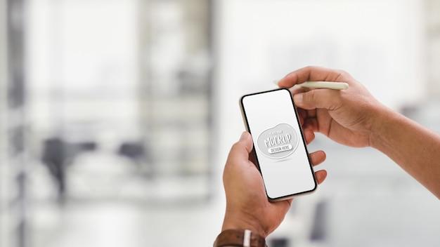 スタイラスペンを押しながらスマートフォンをモックを使用して男性のクローズアップ表示