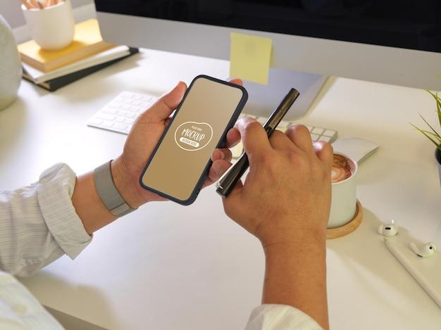 모형 화면으로 스마트 폰을 사용하고 펜을 들고 남성의 뷰를 닫습니다.