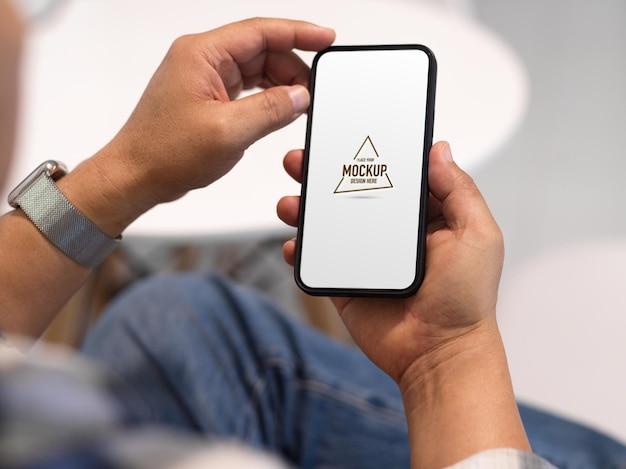 スマートフォンのモックアップを使用して男のフリーランサーの手のビューを閉じる