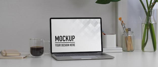 Крупным планом вид макета ноутбука на белом столе с канцелярскими принадлежностями и украшениями в комнате домашнего офиса