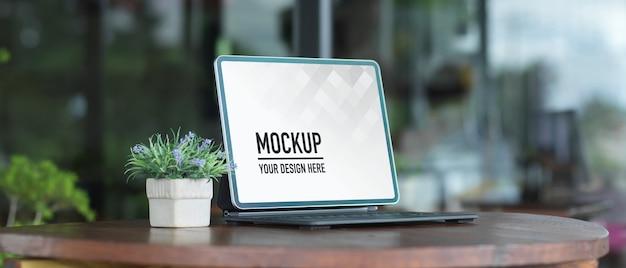 ラップトップと木製のテーブルの植木鉢でポータブルワークスペースのクローズアップビュー