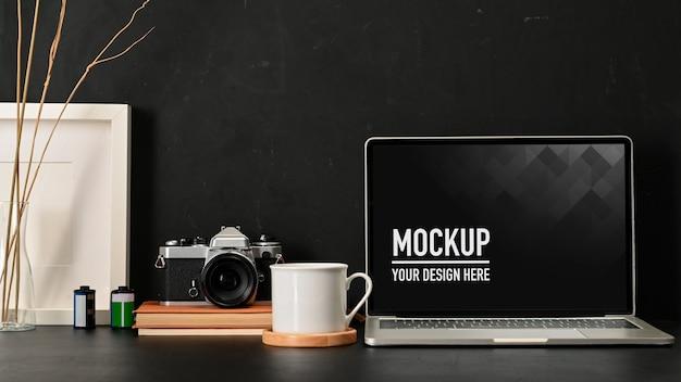 Крупным планом вид рабочего пространства с макетом ноутбука, кофейной кружкой, камерой и принадлежностями