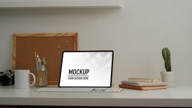 Крупным планом вид рабочего стола с макетом планшета и канцелярских принадлежностей