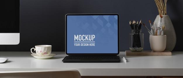 Крупным планом вид рабочего стола с макетом планшета, канцелярскими принадлежностями и компьютерным устройством