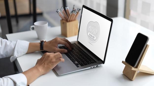 ノートパソコンのモックアップに入力する青年実業家のクローズアップ表示