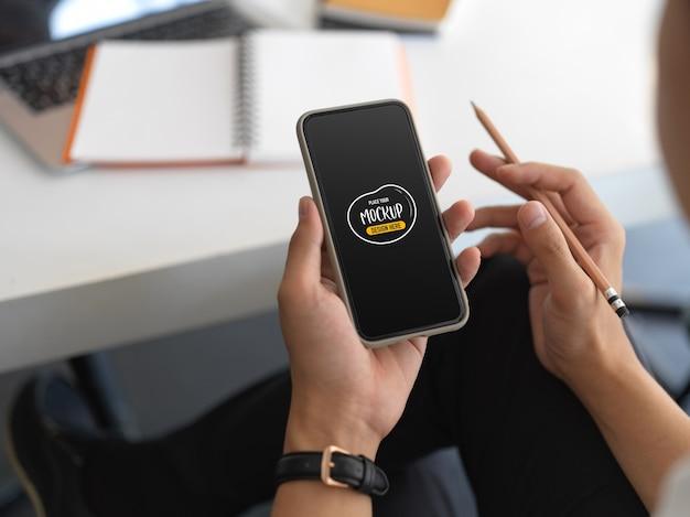 화면 모형과 함께 스마트 폰을 들고 손에보기를 닫습니다.