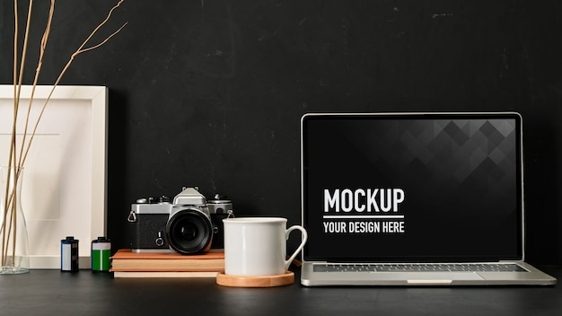 Close up view of workspace with laptop mockup, coffee mug, camera and supplies
