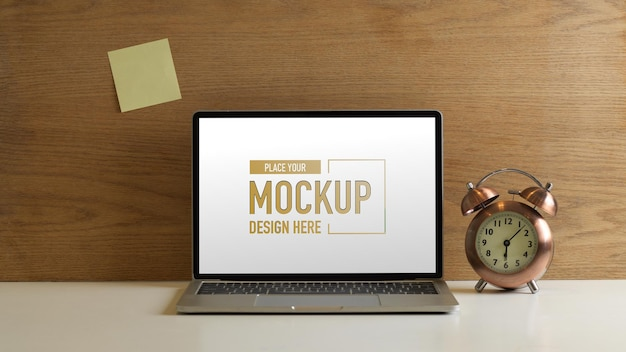 Close up view of workspace with mockup laptop, clock and sticky note on wooden wall