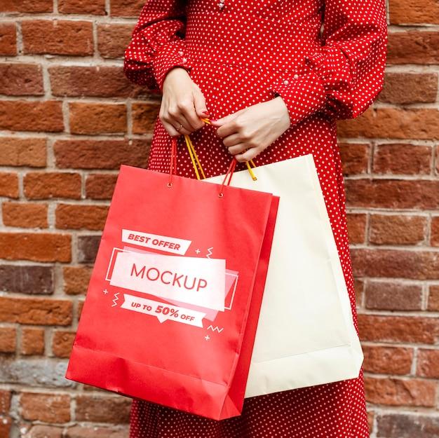 Крупным планом женщина, держащая хозяйственные сумки