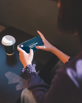 Close up of woman using smartphone in cafe