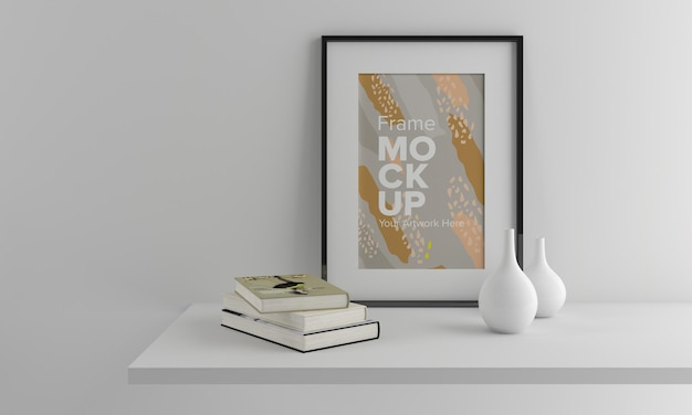Closeup of a black frame mockup on a white wall with a vase and books