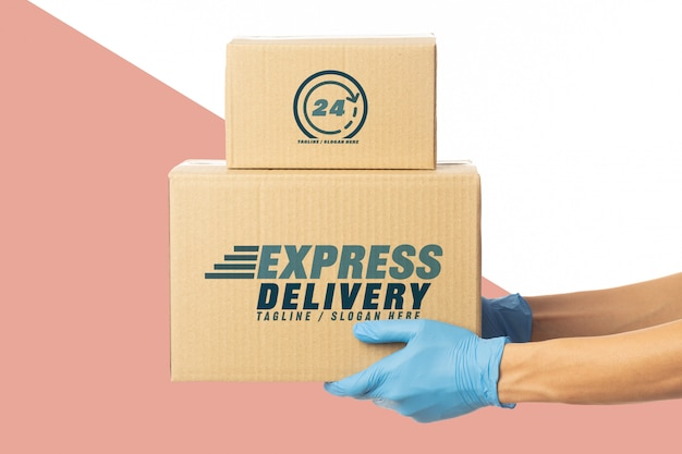 Closeup delivery man hand in medical gloves holding cardboard box mockup template.