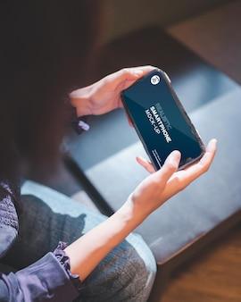 カフェでスマートフォンを使用して女性のクローズアップ。