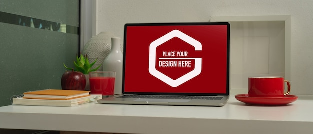 Closeup view of mock up laptop in modern workspace with red coffee cup and decorations