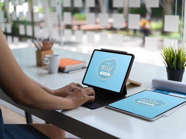 タブレットのモックアップと彼女の事務室でタブレットで入力する女性のクローズアップビュー