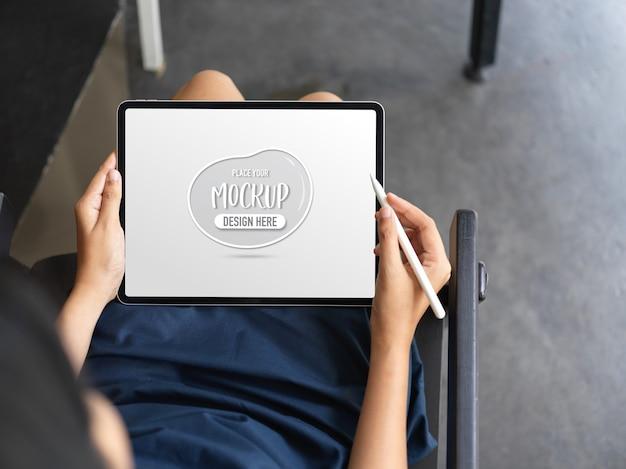 Крупным планом вид женщины, использующей макет планшета, сидя на стуле на своем рабочем месте