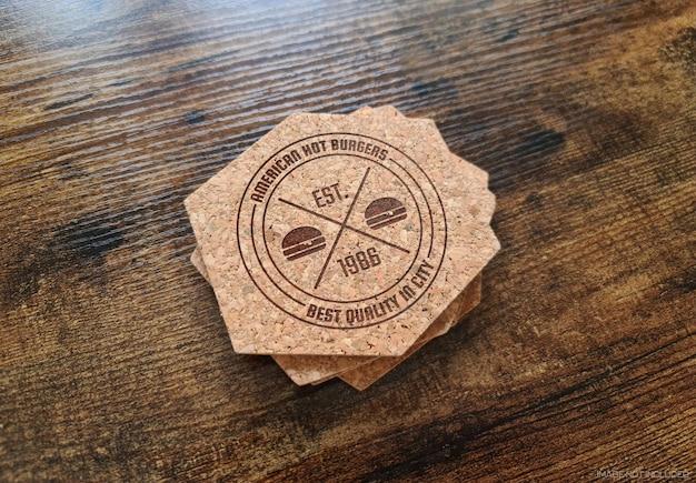 コースターは木の表面のモックアップにロゴを印刷しました
