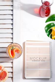 Холодный летний домашний коктейль в бокале с ломтиком грейпфрута и бумажным блокнотом