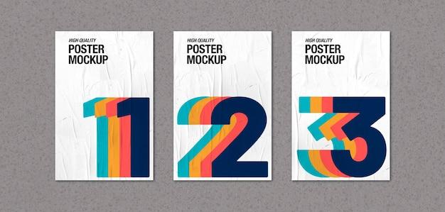 Raccolta di poster accartocciati su mockup di muro di cemento