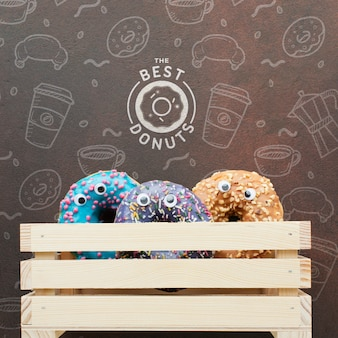Colorful donuts in wooden crate with mock-up