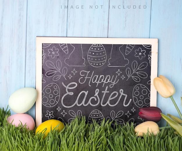 분필 보드 모형과 나무 하늘 표면에 튤립과 다채로운 부활절 달걀