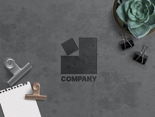 会社のビジネスロゴのモックアップ作業の概念は、オフィス機器でグランジコンクリート表面に刻まれています