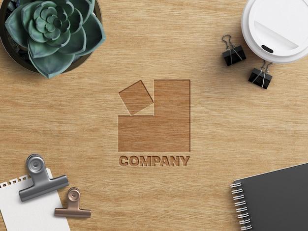 分離された事務機器と木製のテーブルに刻まれた会社のビジネスロゴのモックアップ作業の概念