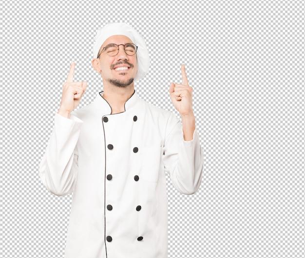 Конкурсный молодой шеф-повар делает жест празднования
